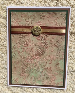 Thistle embossing folder by Anna Griffin colored with crayons and alcohol inks